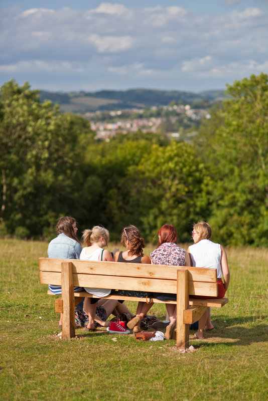 A group of people, walkers taking a break sitting on a bench looking over the Stroud Valley, Cotswolds
