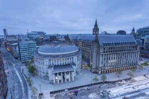 View of St Peter's Square and the local landmark, Manchester Central Library and Manchester Town Hall at dusk.