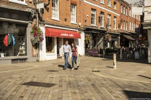 A couple, man and woman having a day out in Winchester, shopping, walking hand in hand passing clothes shop windows, carrying carrier bags.