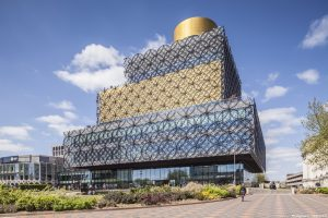 The new Library of Birmingham building with gold and black exterior metalwork detail, and pedestrian square with patterned paving.