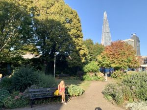 Woman sitting on a bench in a garden where the former church of All Hallows, Southwark, stood, Bankside, London
