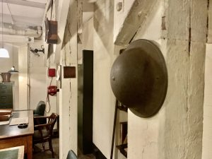 A WW2 steel helmet, known as a tin hat, hangs in the Cabinet War Rooms