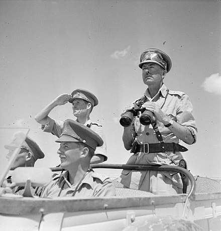 Black and white photo of 4 men in army uniform in a jeep